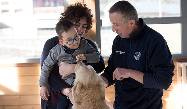 mamma, papà con figlio giocano con cane- Terapia Ricreativa