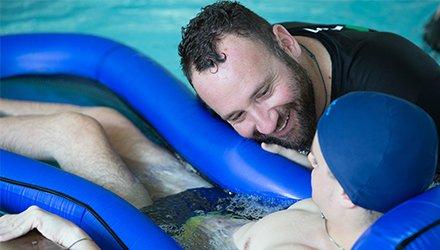 Bambino malato con staff Dynamo fa Terapia Ricreativa in acqua