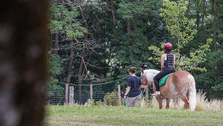 Bambino malato fa attività di Terapia Ricreativa di cavallo
