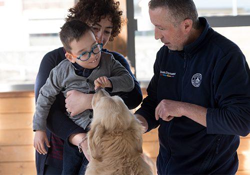 Famiglia ospite a Dynamo Camp sorride e gioca con cane