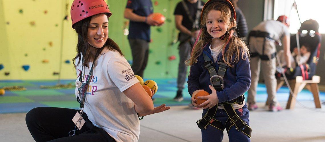 bambina e volontaria giocano con palline in teatro- Terapia Ricreativa