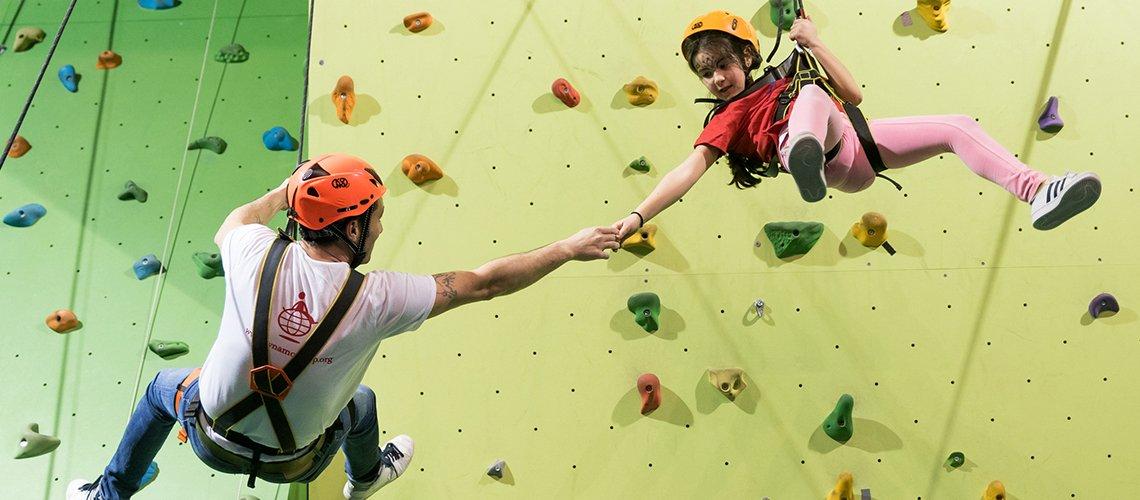 Bambino fa attività di arrampicata con staff a Dynamo Camp